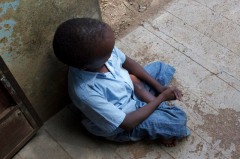 A primary school pupil at Joyland sits alone outside his dormitory