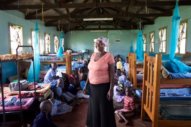 A caretaker with some of the pupils in the girl's dormitory