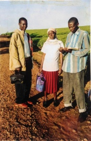 Nyanya (far left), at age 18, walking to church in Kericho, along a road edged by tea fields.